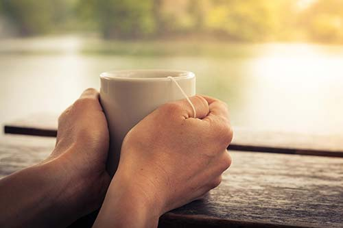 Hands holding cup of tea looking towards lake